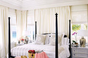 A four poster bed in a whitewashed beach house bedroom
