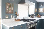 This is a blue/green farmhouse kitchen with stainless steel appliances and lots of natural light.