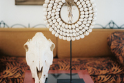 A skull and a beaded neck piece on a red side table