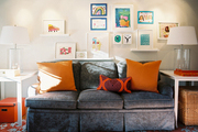 A gallery wall of children's art above a gray couch and an orange floral-patterned rug