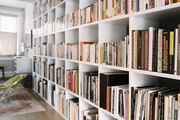 A grid of white shelves filled with books