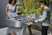 Bridgid Coulter's daughters, Tai and Imani, play foosball in the backyard over oriental rugs