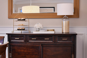 A gold mirror compliments the wooden buffet table's gold accents.