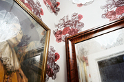 A vintage light fixture in a bedroom with floral-print wallpaper