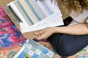 Textile designer Bridgid Coulter sketches patterns on a Kantha blanket in her backyard