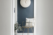 A view of a painted blue wall in a white hallway with a metal chair.