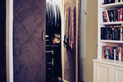 Upholstered closet doors and a patterned carpet in a bedroom with built-in bookcases