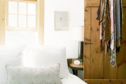 Ties hung on a wooden door beside a bed dressed in white bedding
