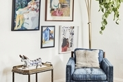 A gold floor lamp behind a blue armchair beside a gallery wall of paintings.
