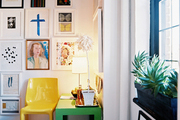 A green Parsons table and a yellow molded-plastic chair below a gallery wall of art