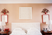 A white tufted headboard between a pair of wooden bedside tables