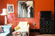 Red lacquered walls and ceiling with framed art and midcentury furniture