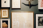 A grouping of framed art on gray walls