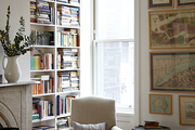 A sitting area near a fireplace and a floor-to-ceiling built-in bookshelf