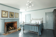 A blue bedroom with a very statement making light fixture.