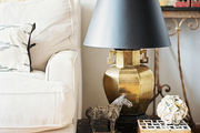 A brass lamp with a black lampshade beside a white couch