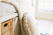 A cozy white knit and pillows on the sofa.