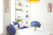 White walls and built in bookshelf surrounding the corner bench and circular table.
