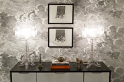 Artwork and a pair of Lucite table lamps on a console against cloud-patterned wallpaper