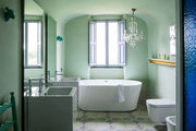 A bathroom with terrazzo floors, a contemporary soaking tub and square sinks, and a crystal chandelier