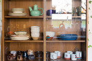 Colorful pottery and glassware is displayed in a wooden cabinet.