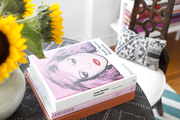 Art books and a vase of flowers sitting on a table