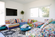 A multicolored, bold printed couch with a contrasting black and white retro printed rug.