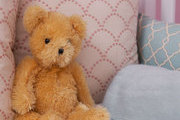 A stuffed teddy bear mingles with throw pillows by Loom Decor