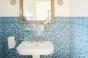 Blue-and-white tile and a pedestal sink in a powder room