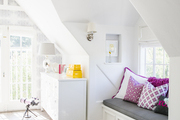 Purple pillows add color to an all-white kid's room