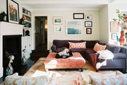 A purple sectional couch and a pink tufted ottoman atop a patterned rug