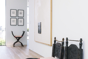 A sleek hallway with ethnic chairs and contemporary art