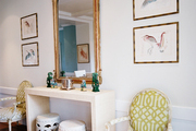 White garden stools and a gold mirror between a pair of upholstered chairs