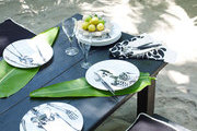 A tropical tabletop set with palm leaves and skeleton-motif plates.