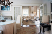 White french doors separating a neutral dining room and living room