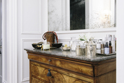 A wooden set of drawers serving as a vanity in a master bath