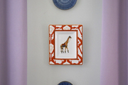 Decorative plates mounted on a gray wall and framed by purple curtains in a home designed by BHDM.