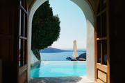 An arched doorway with views of an infinity pool and the ocean