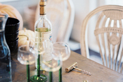 Green-stemmed wineglasses on a table surrounded by white chairs