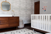 Striped rug and patterned walls in a nursery.