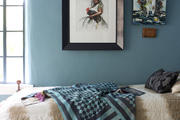 A bed with a throw pillow and a kantha quilt; framed art on display