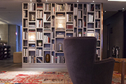 A compartmented bookshelf, velvet chair, and patchwork rug in the lobby of Belgraves Hotel, designed by Tara Bernerd & Partners