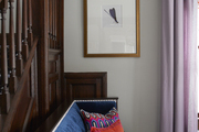 A blue velvet settee next to a stairway