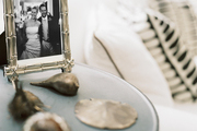 A round side table covered with a framed photograph and silver seashells