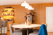 A wooden dining room with white pendant lights.