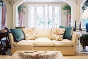 An white couch paired with an ottoman made from a leopard rug