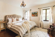 A Spanish-style neutral bedroom with white walls and a beige bed.