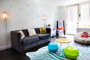 Colorfully vivid window-lit room with fun round seating and a big comfy couch.