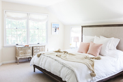 A contemporary, neutral bedroom with pink accent pillows.