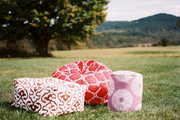 A trio of patterned poufs on a grass lawn